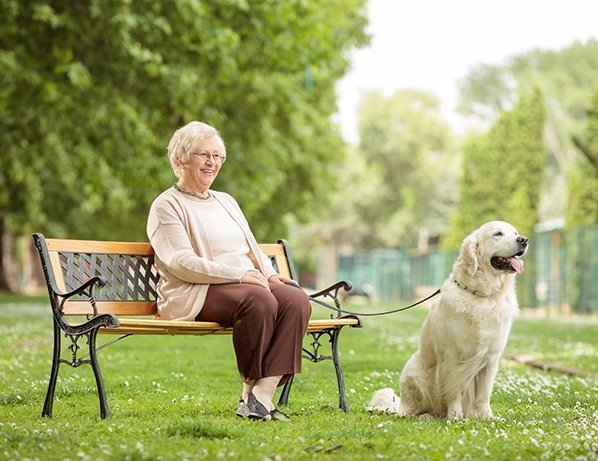 Senior woman at park sitting with dog