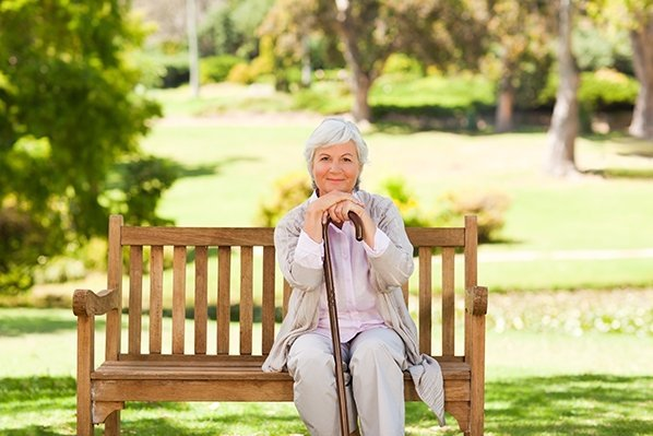 woman with walking-stick sitting at park