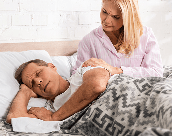 worried woman waking snoring husband bed